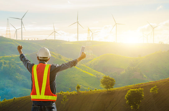 Successful engineers stand at the wind turbines against the backdrop of the sunrise.