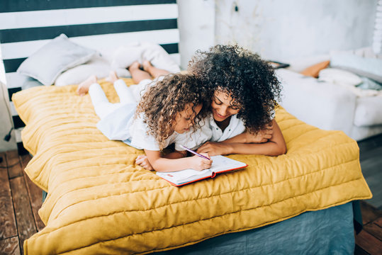 Black mother and daughter lying on bed and doing homework together