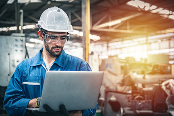 Confident engineer in blue jumpsuit holding laptop computer in a warehouse. Fotobehang