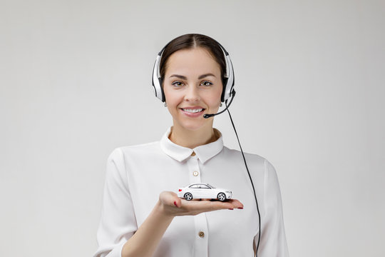 Car insurance. Beautiful smiling woman consultant of call center in headphones holding white car on gray background. female customer support operator with headset