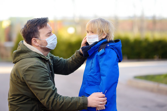 Mature man wearing a protective mask puts a face mask on a his son in airport, supermarket or other public place. Safety during COVID-19 outbreak.