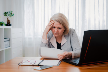 older Senior woman struggles at the computer with paper documents, puzzled by the business decision