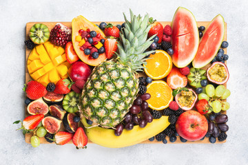 Wall Mural - Healthy raw rainbow fruit platter mango papaya strawberries oranges blueberries pineapple watermelon on wooden board on white concrete background, top view, selective focus