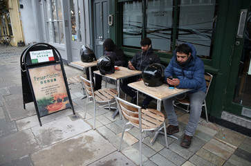 Food delivery drivers outside a restaurant waiting for work near Primrose Hill in London