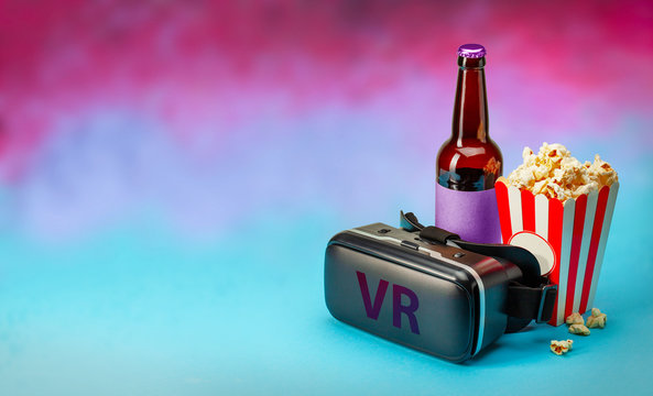 VR movie at home. VR glasses helmet and popcorn and bottle of beer on colorful background. Copy space for text