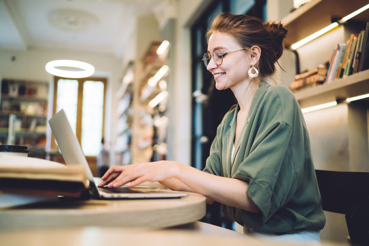 Cheerful young freelance woman typing on laptop in library