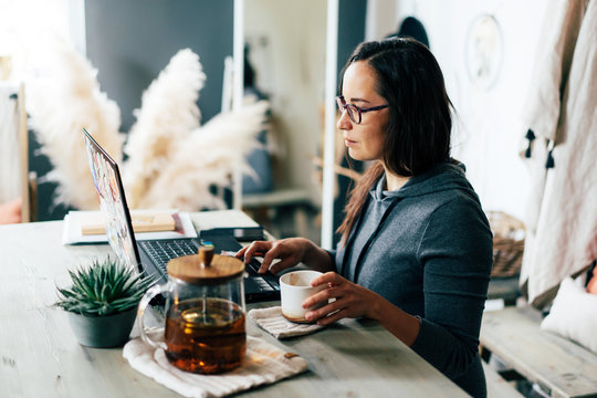 A brunette in glasses works on a laptop. Work from home or from a cozy cafe.