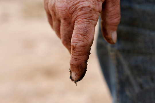 Oil is seen on the finger of Paul Putnam, 53, an independent contract pumper in Loving County