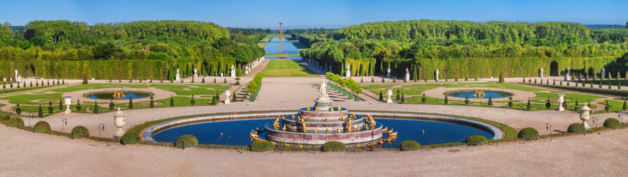 Panoramic view of the Versailles Park - the Latona Basin with the Grand Canal in the background under the summer sun, Versailles, France