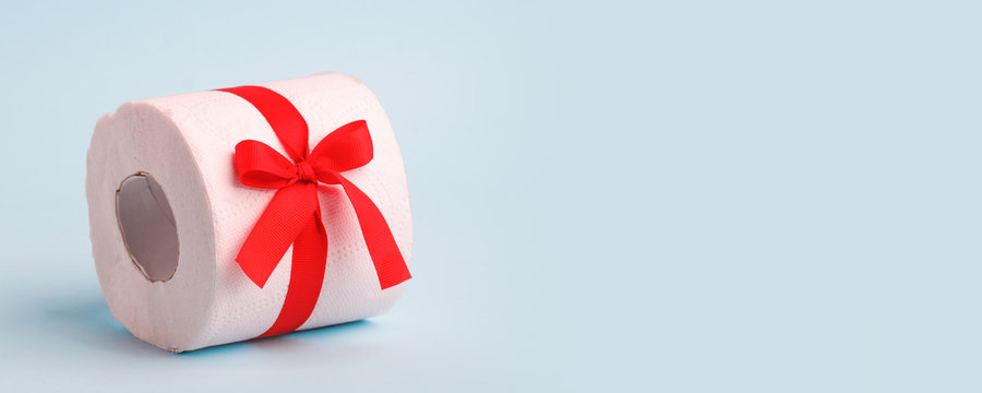 A roll of toilet paper wrapped in a gift bow. The concept of a valuable actual gift, a meme on the deficit in supermarkets, coronavirus covid-19, panic, excitement and shortage of goods, banner