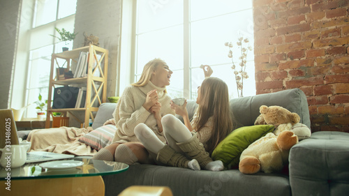 Stay home together. Happy loving family. Mother and daughter spending time together at home. Watching cinema, using laptop, laughting. Mother's day, celebration, weekend, holiday childhood concept.