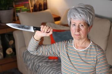 Senior woman holding a knife