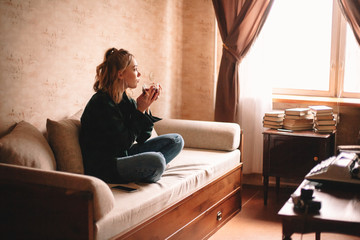 Young thoughtful woman drinking tea and eating chocolate while looking through window sitting on sofa in living room at home Wall mural