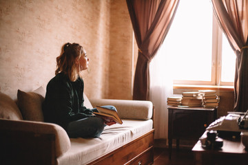 Young thoughtful woman holding book looking through window while sitting on sofa in living room at home
