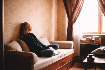 Young upset woman holding book looking through window while sitting on sofa in living room at home