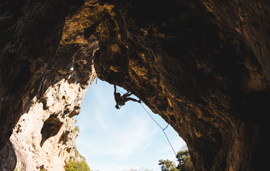 Rock climber climbs into the cave.