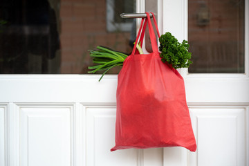 Shopping bag with goods and food is hanging at the front door, neighborhood help concept at...