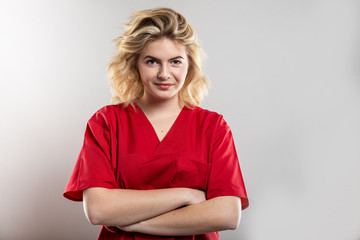 Portrait of nurse wearing red scrub standing with arms crossed