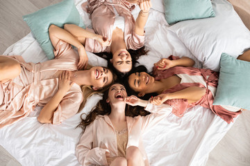 Top view of multiethnic women smiling and lying on bed at bachelorette party