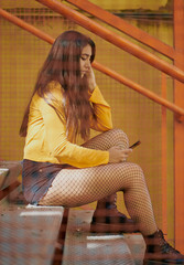 girl sitting on some stairs and orange colors seen through a fence