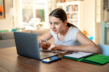 Teenager girl studying online at home looking at laptop at  quarantine isolation period during...