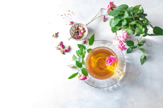 Pink tea buds, a glass cup and vintage strainer.