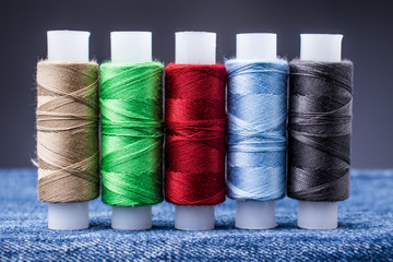 Several spools of colored thread for sewing on denim. Concept needlework and tailoring.
