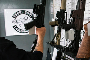 A man holds a gun displayed at Shore Shot Pistol Range gun shop, amid fears of the global growth of coronavirus disease (COVID-19) cases, in Lakewood Township, New Jersey