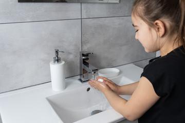 Obraz Dziewczynka myje ręce w łazience. Mycie i dezynfekcja rąk mydłem i płynem antybakteryjnym. - fototapety do salonu