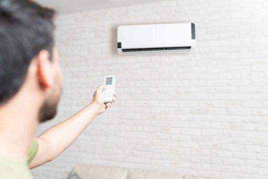 Man Adjusting Temperature Of Air Conditioner