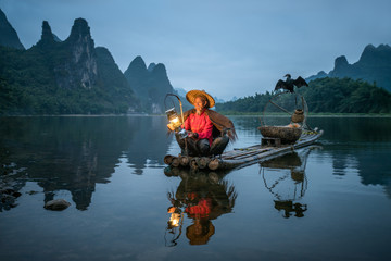 Old Chinese fisherman with cormorant on the Li river, Guilin, China