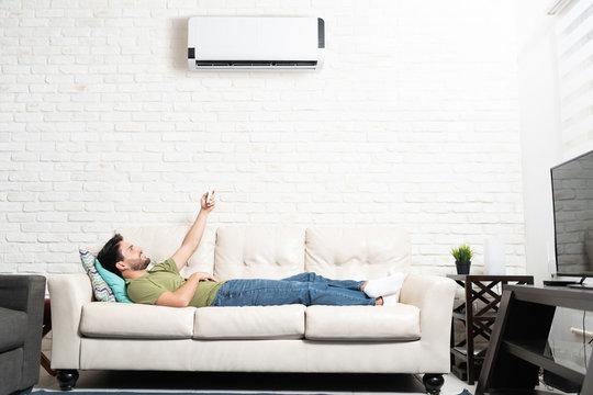 Man Turning On Mini Split At Home