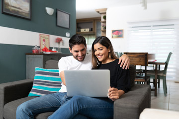 Smiling Couple Using Laptop At Home Wall mural