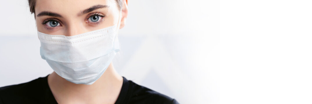 Portrait of a girl in a disposable facial mask. Coronavirus epidemic. Covid-19 protection. Quarantine all over the world. White background