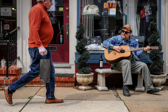 John Schumaker plays guitar on the sidewalk below his apartment on Maryland Ave. while an unidentified man strolls by wearing a glove to prevent the spread of coronavirus disease (COVID-19) in Annapolis