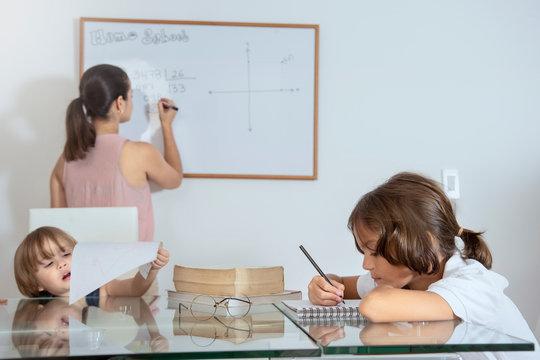 Madre enseñando en casa a sus hijos