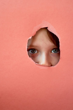 Quarantine, isolation. A child looks out of a hole torn in the paper. Child's fear. Loneliness.
