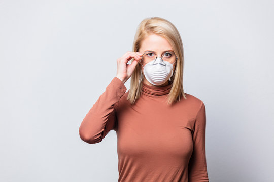 Beautiful blonde woman in glasses and face mask on white background