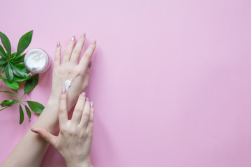 Aluminium Prints Manicure Natural Cosmetics for hand skin care with cream bottle, a means to reduce wrinkles on hands, moisturizing. Beautiful woman's hands on the pastel pink background.