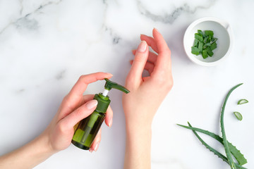 Woman applying organic moisturizer hand cream. Aloe vera lotion bottle in female hands and sliced plant stems on marble background. Hands dermatology and skin treatment concept. Flat lay, top view