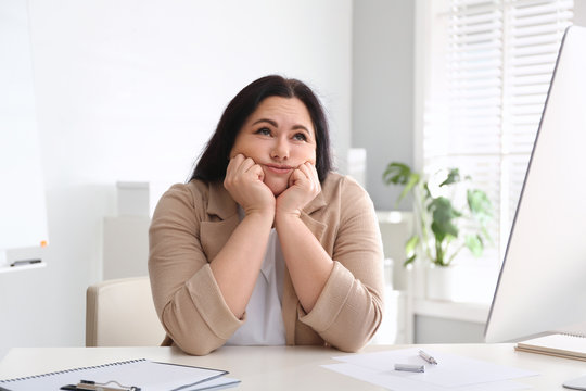 Lazy overweight worker at white desk in office