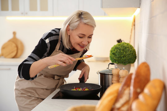 Mature woman cooking on stove in kitchen