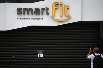 A man takes pictures of a notice inviting people to join Smart Fit gym's online workout classes at home, as the gym suspends training sessions as a protective measure to prevent the spread of the novel coronavirus disease (COVID-19) in Sao Paulo