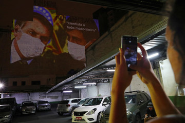 A woman takes a picture of an image depicting Brazil's President Jair Bolsonaro and Health Minister Luiz Henrique Mandetta, projected on the wall of a building as a protest, following the coronavirus disease (COVID-19) outbreak in Sao Paulo