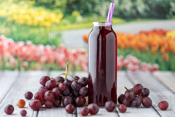 A close up view of a glass bottle of grape juice surrounded by grapes against a garden background. Fototapete