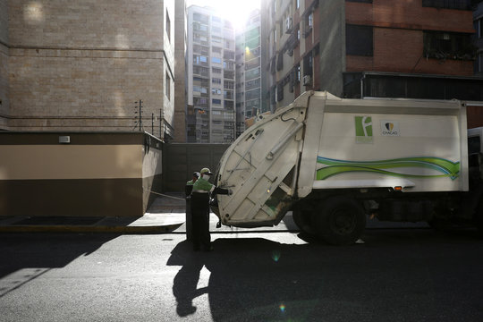 A municipal worker collects garbage in a neighbourhood as Venezuelan utilities have hiked fees while the economy deteriorates further due to the spread of coronavirus disease (COVID-19) and the crash in global oil prices, in Caracas