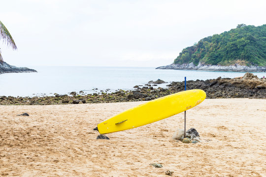 Yellow surfboard on the sand beach with the rock beach at the background, water sport and activity