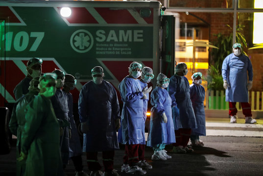 Health workers in protective gear stand next to ambulances parked near the entrance of the ferry company Buquebus at the Buenos Aires docks after a passenger was suspected to have contracted the coronavirus disease (COVID-19), in Buenos Aires