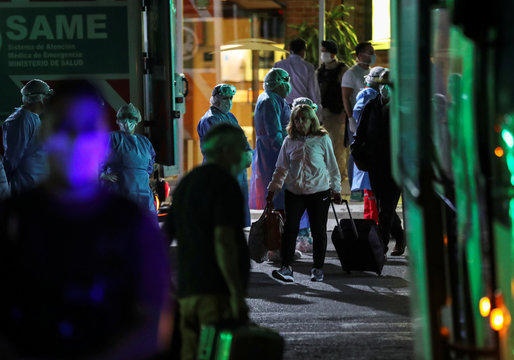 A passenger who travelled with the ferry company Buquebus walks towards a bus that will transport her and all other passengers for quarantine after one of them was suspected to have contracted the coronavirus disease (COVID-19), at the Buenos Aires docks