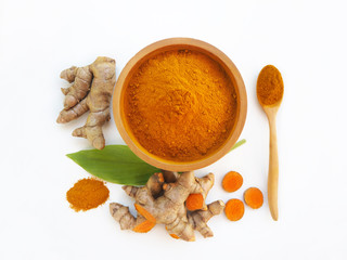 Fototapeta turmeric powder or curcuma longa in a wood bowl with spoon and green leaf and use as ingredients cosmetics products and is a anti inflammatory, antioxidant, including is a herb use for health care. obraz